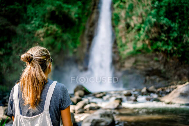 Back view of young woman sitting on stone near calm lake and magnificent waterfall on sunny day — Stock Photo