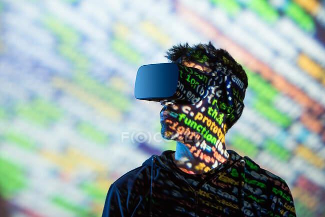 Varón barbudo irreconocible con capucha y auriculares modernos que exploran la realidad virtual con luz de neón - foto de stock
