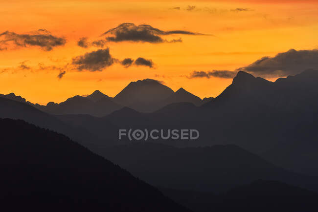 Breathtaking view of silhouettes of mountain peaks on background of bright orange sundown sky — Stock Photo