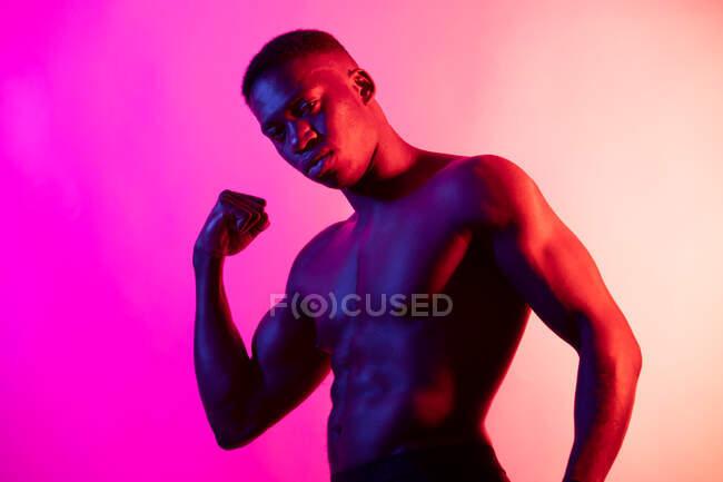 Впевнений молодий атлетичний чорний хлопець з голим тулубом дивиться на камеру, тримаючи руки в кулаках студії на неоновому рожевому фоні. — Stock Photo