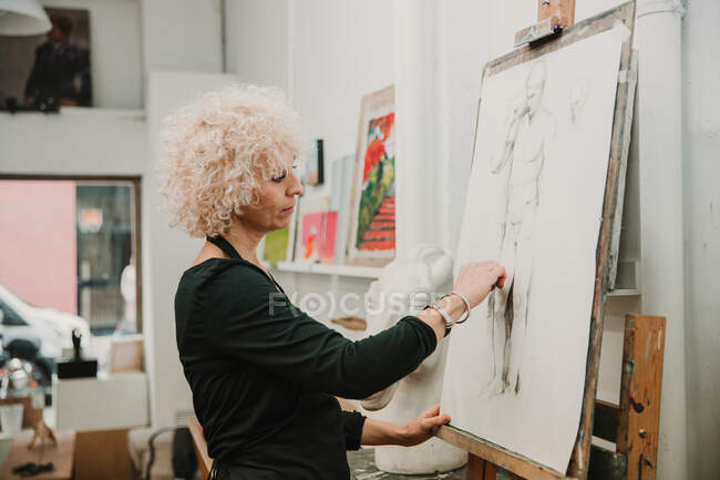 Female artist creating drawing of human with pencil while standing at easel in studio — Stock Photo