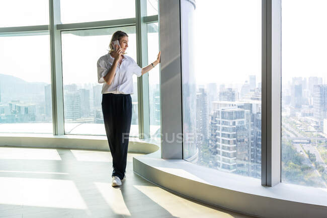 Lonely girl in empty office calling with her cell phone while looking the city scape through the windows — Stock Photo