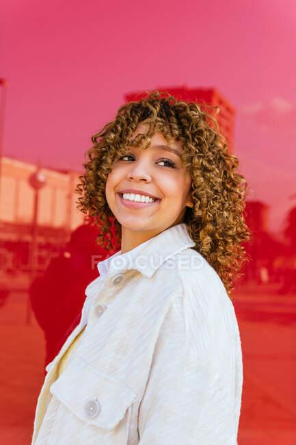 Encantada hembra afroamericana con peinado rizado de pie sobre fondo rojo en el estudio mirando hacia otro lado - foto de stock