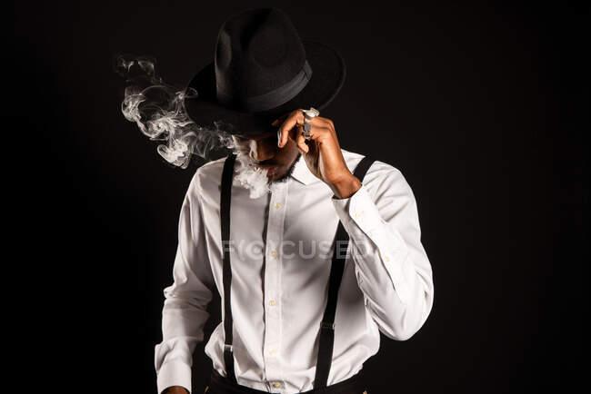 Masculino afroamericano masculino en camisa blanca y sombrero exhalando vapor mientras fuma cigarrillo electrónico - foto de stock