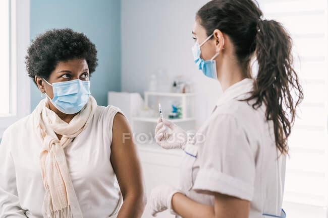 Especialista médica feminina em uniforme de proteção, luvas de látex e máscara facial vacinando a paciente madura afro-americana na clínica durante o surto de coronavírus — Fotografia de Stock