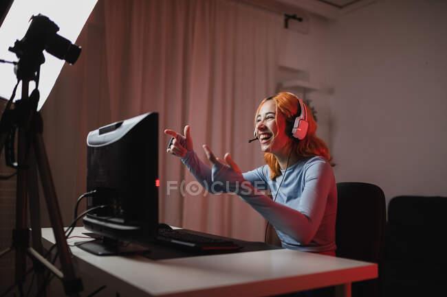 Smiling female gamer in headphones recording video on professional camera for social media blog — Stock Photo