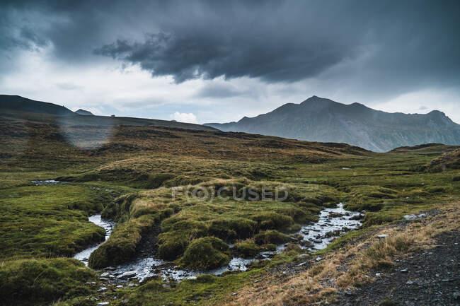 Impresionante paisaje de prado con hierba verde y arroyo que fluye sobre colinas bajo el cielo sombrío en los Pirineos en España - foto de stock