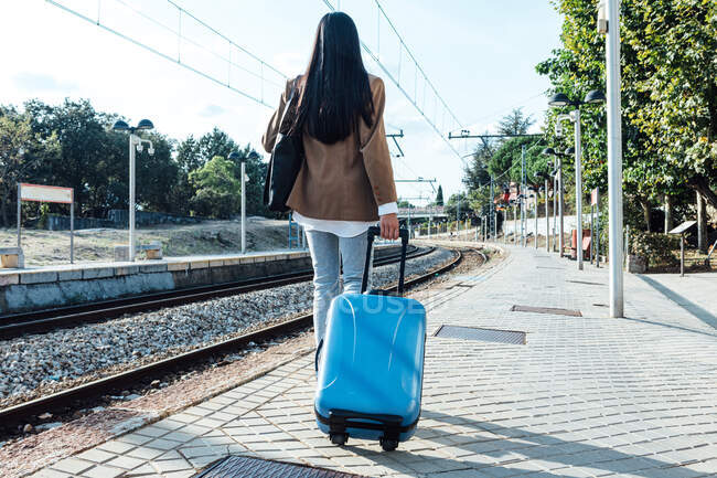 Back view of anonymous female traveler with suitcase walking along platform at railway station on sunny day — Stock Photo