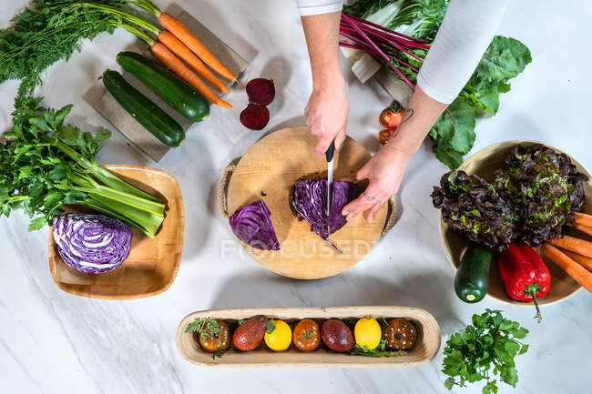From above cropped unrecognizable female cutting red cabbage with knife while preparing vegetarian food at table in loft style house — Stock Photo