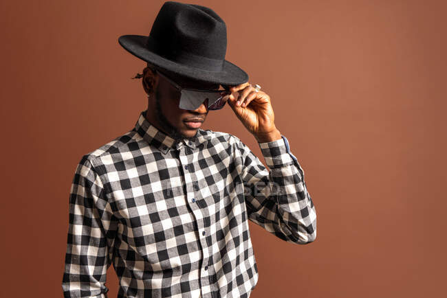 Young cool African American male model in checkered shirt, hat and sunglasses while standing on brown background — Stock Photo