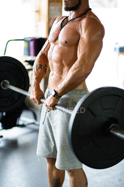 Cultivado atleta masculino fuerte irreconocible haciendo deadlift con barra pesada durante el entrenamiento en el gimnasio - foto de stock