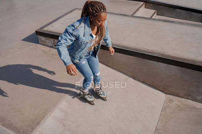 From above of cool African American female in denim clothes rollerblading in skate park on sunny day in summer — Stock Photo