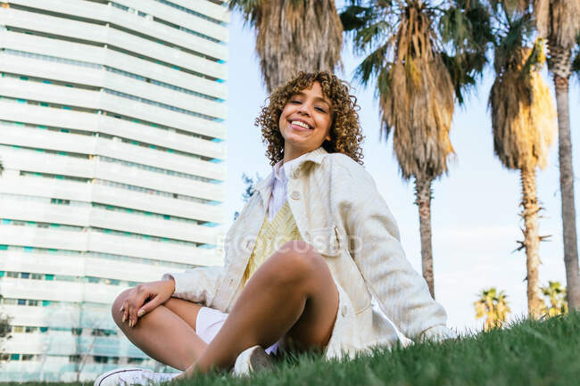 From below of glad black female in stylish outfit sitting on lawn with palm trees in city and looking at camera — Stock Photo