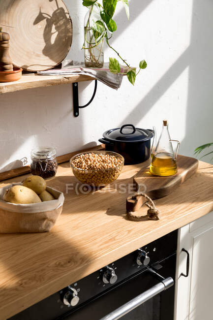 Assorted ingredients and utensils placed on wooden table during cooking process in home kitchen with white wall and minimalistic interior in natural eco friendly style — Stock Photo