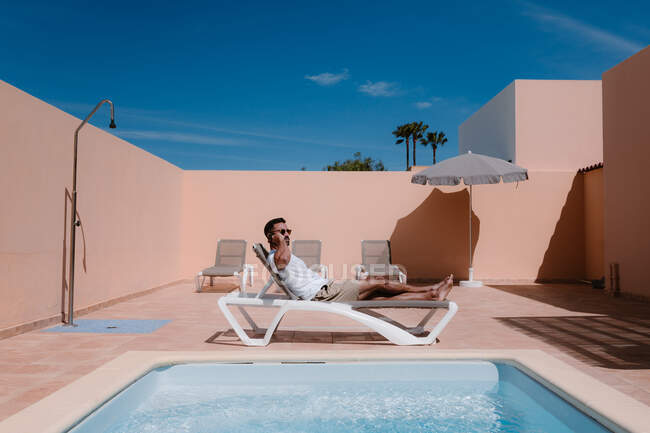 Side view of male freelancer lying on lounger at poolside and speaking on mobile phone during telework in summer on sunny day — Stock Photo