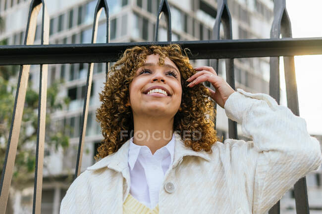 Side view of charming smiling black female with curly hair leaning on metal fence in city and looking away — Stock Photo