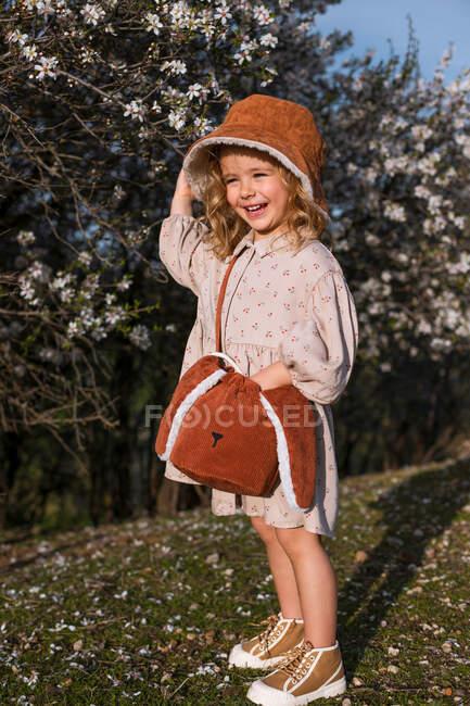 Adorable niño sonriente en vestido de pie cerca del árbol en flor con flores en el parque de primavera y mirando hacia otro lado - foto de stock