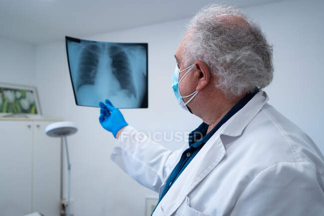 Vista lateral del anciano médico en máscara y guantes examinando la imagen de rayos X de los pulmones del paciente durante el coronavirus en el hospital - foto de stock