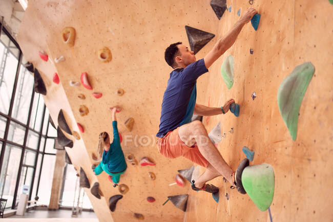 Side view of strong male and female climbers climbing artificial wall in bouldering club — Stock Photo