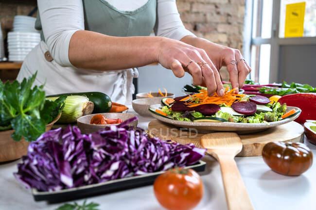 Cultivo hembra irreconocible con zanahoria cruda preparando comida vegetariana en la casa cocina moderna - foto de stock