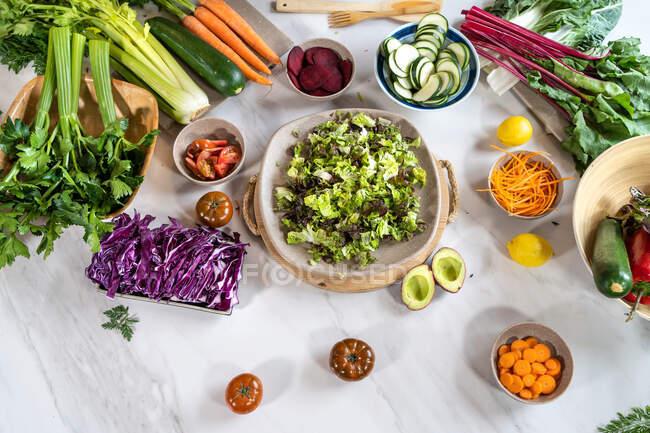 Vista superior de verduras enteras y cortadas para la preparación de ensaladas en mesa de mármol - foto de stock