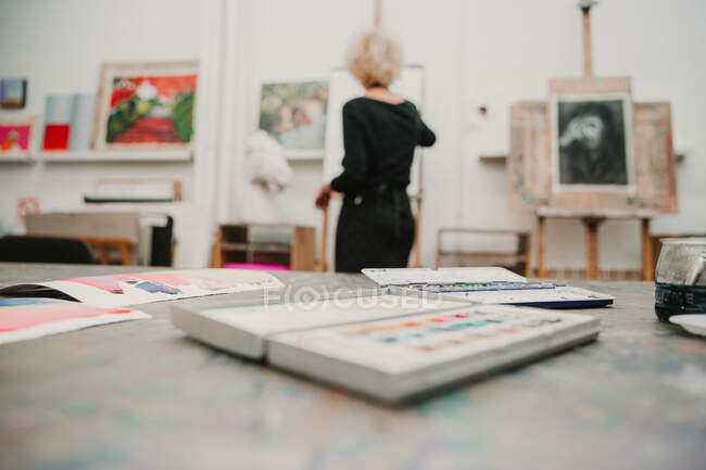 Low angle of table with art supplies placed on background of anonymous female artist standing at easel and painting — Stock Photo