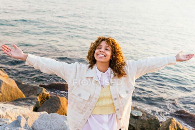 Високий кут веселої афро-американської жінки стоїть з розпростертими руками на скелях на узбережжі і насолоджується свободою під час заходу сонця. — стокове фото