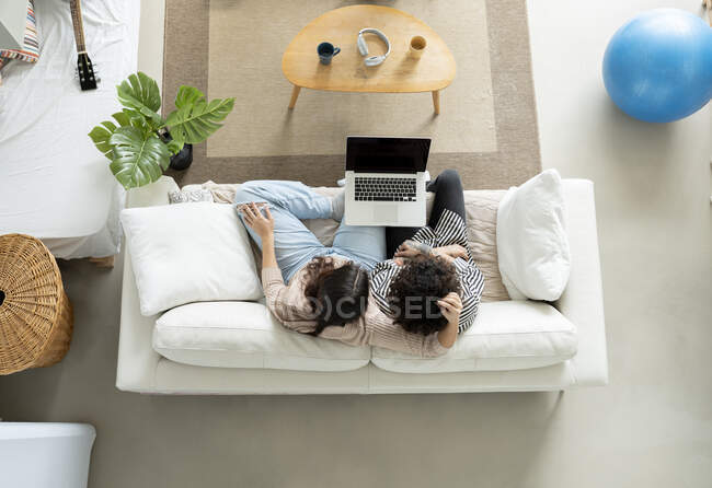 From above couple browsing laptop on couch in house room — Stock Photo