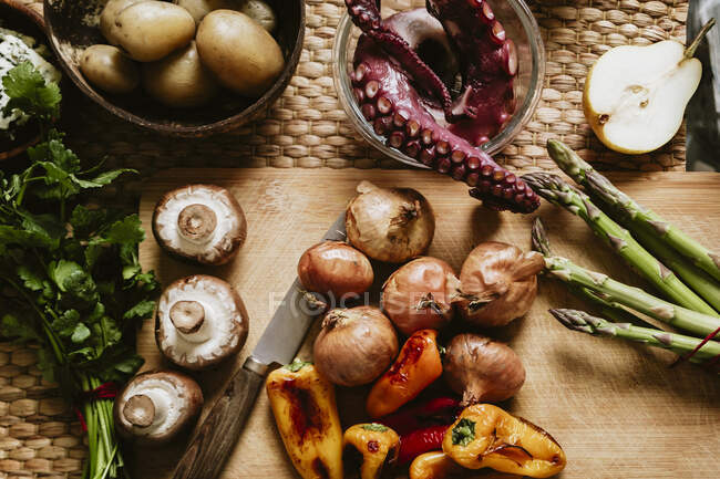 From above of grilled peppers with mushrooms and onions on chopping board against cooked octopus in bowl on table — Stock Photo