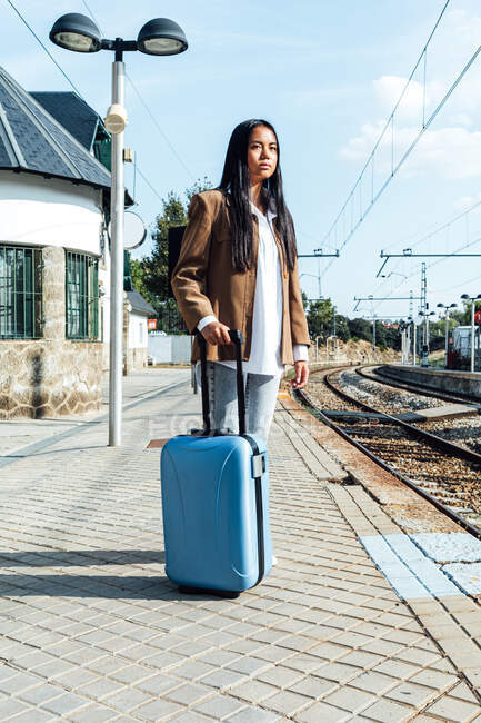 Side view of Asian female traveler with suitcase standing on platform of railroad station while waiting for the train — Stock Photo