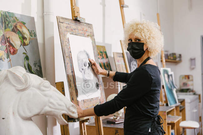 Side view of talented female artist standing at easel and drawing on paper with pencil in art studio — Stock Photo
