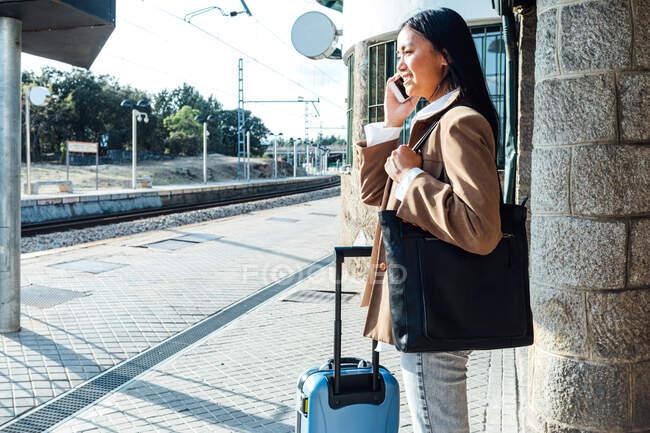 Сторона зору етнічної жінки-мандрівника стоїть з валізою на платформі на залізничній станції і розмовляє на смартфоні. — стокове фото