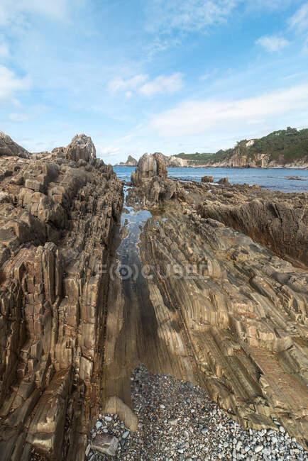 Vista panoramica delle formazioni rocciose sulla spiaggia di Gueirua vicino al mare calmo sotto il cielo blu nelle Asturie — Foto stock