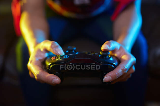 Crop unrecognizable gamer using joy pad and playing video game in dark room — Stock Photo