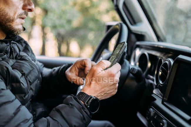 Crop vista di uomo irriconoscibile utilizzando il suo cellulare all'interno della macchina prima di iniziare a guidare — Foto stock