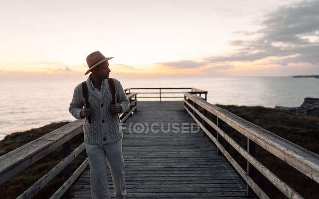 Man with backpack and hat standing on a walkway looking at the sea — Stock Photo