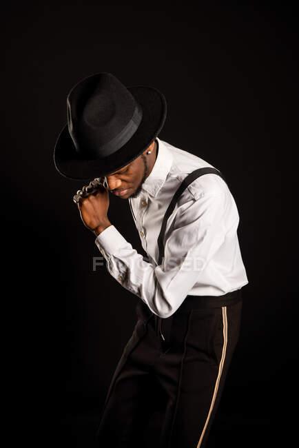 Joven modelo masculino masculino étnico en sombrero y pantalones de pie bailando sobre fondo negro - foto de stock