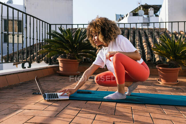 Focused African American female with curly hair choosing online tutorial on laptop while sitting on mat on rooftop and preparing for yoga lesson — Stock Photo