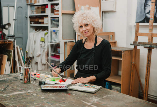 Focused female artist sitting at table and painting with watercolors on paper while working in creative workshop — Stock Photo