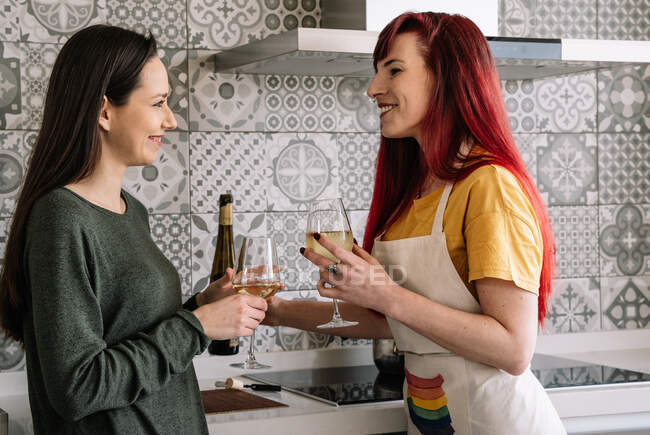 Side view of young smiling homosexual women with glasses and bottle of white wine speaking in house while looking at each other — Stock Photo