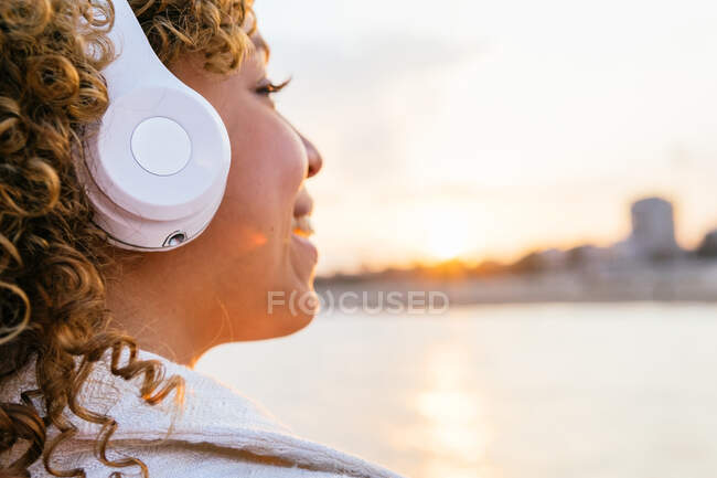 Side view of cropped cheerful black female in wireless headphones enjoying music on seashore in evening — Stock Photo