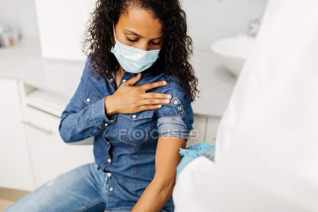 Especialista médico masculino irreconocible en uniforme protector y guantes de látex vacunando a una paciente afroamericana en la clínica durante el brote de coronavirus - foto de stock