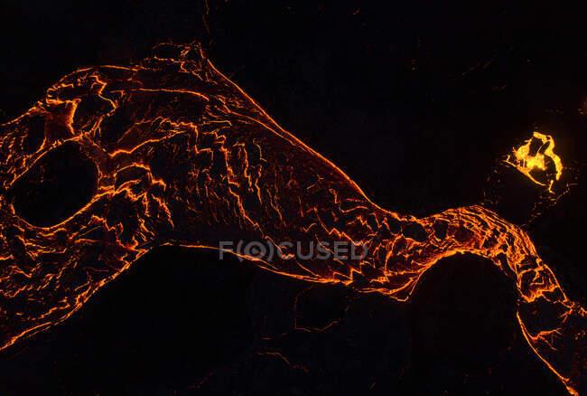 Desde arriba el magma del volcán corre en forma de ríos de lava a través del suelo en Islandia - foto de stock