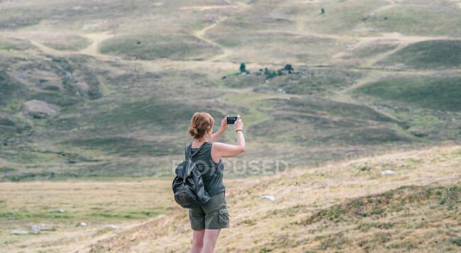 Vista posteriore di anonimo zaino in spalla femminile scattare foto di colline sul cellulare durante il viaggio estivo alla luce del sole — Foto stock