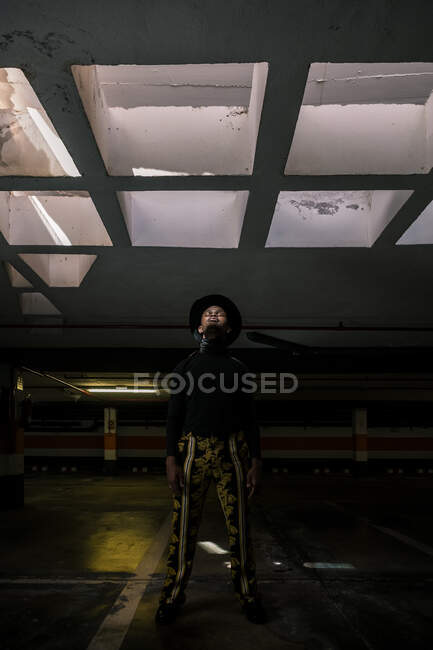 Trendy African American male lit by sunlight standing in dark underground parking and looking away — Stock Photo