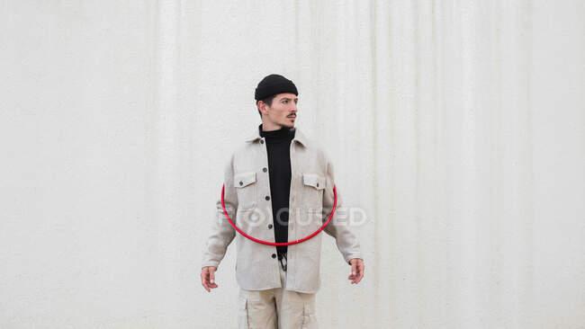 Впевнений чоловік у модному одязі стоїть з червоним гімнастичним обруч біля сірої стіни будинку в місті і дивиться на камеру. — стокове фото