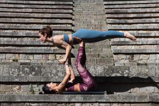 Вид сбоку гибкой поддерживающей женщины на ногах во время совместной практики акро-йоги на каменной лестнице — стоковое фото