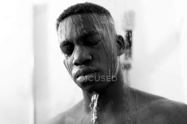 Black and white of emotionless young black guy taking shower in light bathroom with closed eyes and water on face — Stock Photo