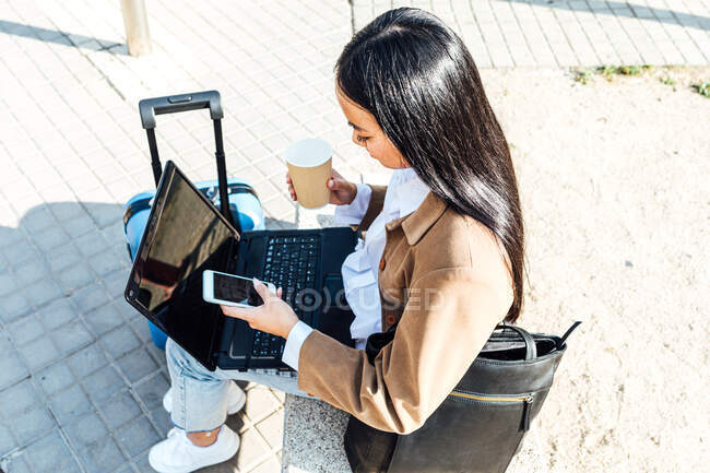 From above side view of Asian female freelancer sitting on bench with laptop and takeaway coffee and browsing smartphone while waiting for train at railway station and working remotely — Stock Photo