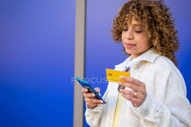 Content stylish African American female paying with plastic card during online shopping via mobile phone while standing on blue background in studio — Stock Photo